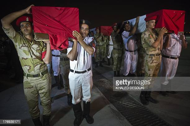 Egyptian army and policemen carry coffins covered with the national flags at Almaza military Airbase in Cairo on August 19 during a funeral for 25...