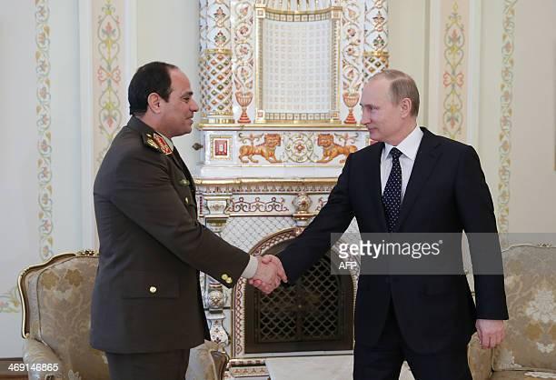 Egyptian army chief Abdel Fattah alSisi shakes hands with Russian President Vladimir Putin during their meeting in NovoOgaryovo residence outside...