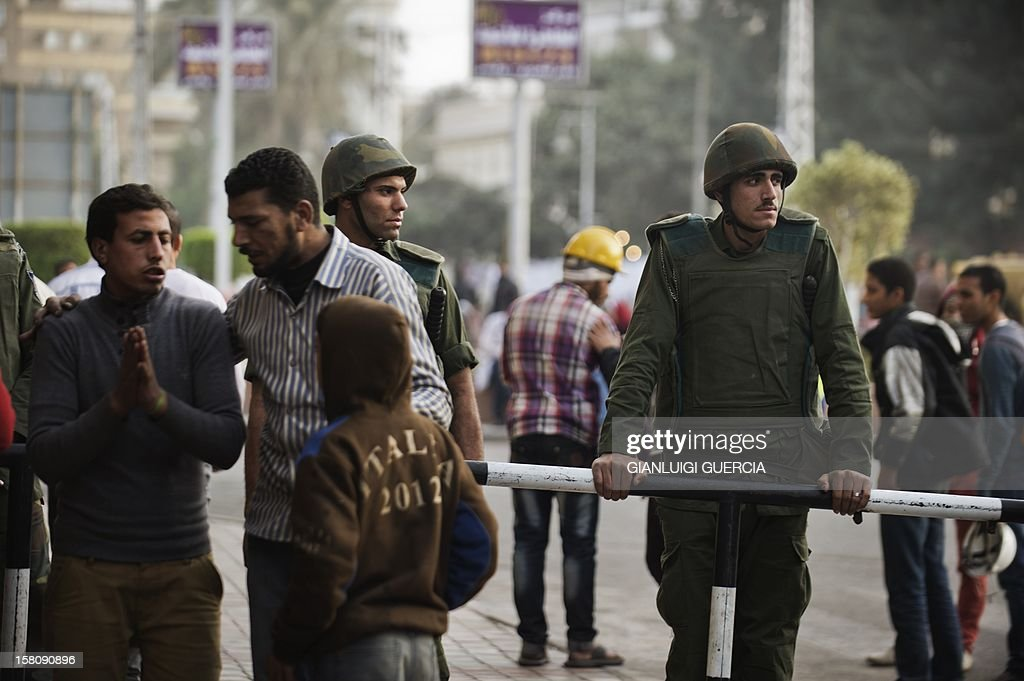 Egyptian army soldiers stand by as opposition protesters man a checkpoint outside the presidential palace area where they are gathering on December 10, 2012 in Cairo. President Mohamed Morsi has ordered Egypt's army to 'cooperate' with police and given it powers of arrest until the results of a referendum to be held this weekend, according to a decree obtained by AFP. The decree, which appears in the government's latest official gazette under 'Law 107', was issued ahead of rival mass protests called by pro- and anti-Morsi camps over the referendum. AFP PHOTO/GIANLUIGI GUERCIA