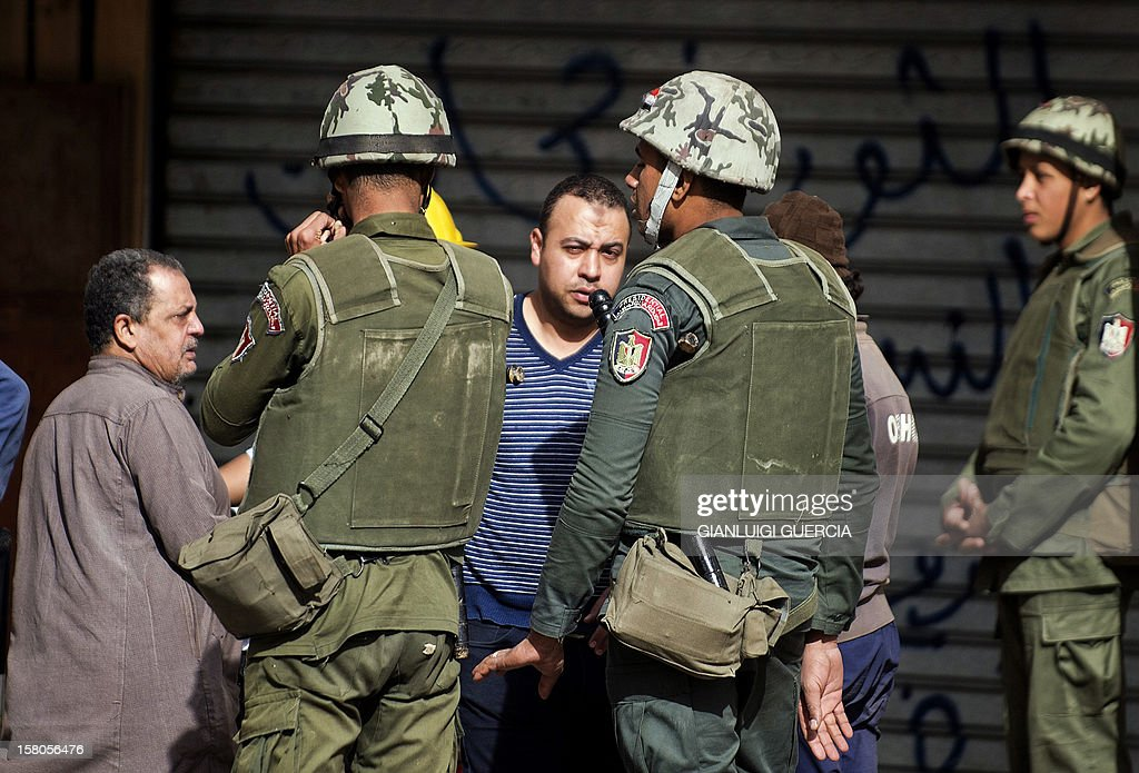 Egyptian army soldiers stand guard as opposition protesters check identification cards at the entrance of the area outside the presidential palace in Cairo where opposition supporters are gathering on December 10, 2012, ahead of expected demonstrations later in the week. President Mohamed Morsi has ordered Egypt's army to 'cooperate' with police and given it powers of arrest until the results of a referendum to be held this weekend, according to a decree obtained by AFP.