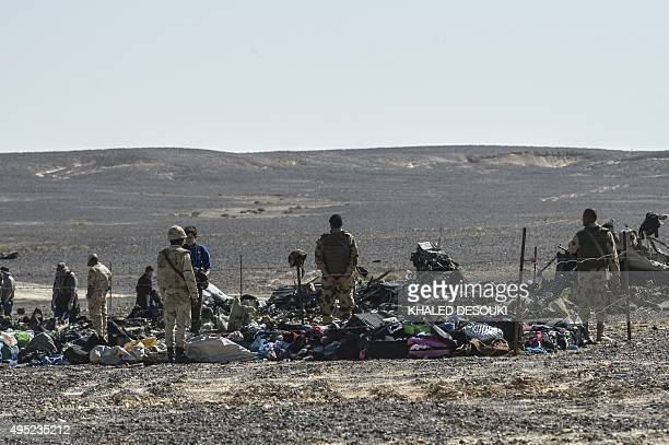 Egyptian army soldiers stand guard next to debris and belongings of passengers of the A321 Russian airliner that crashed the previous day in Wadi...