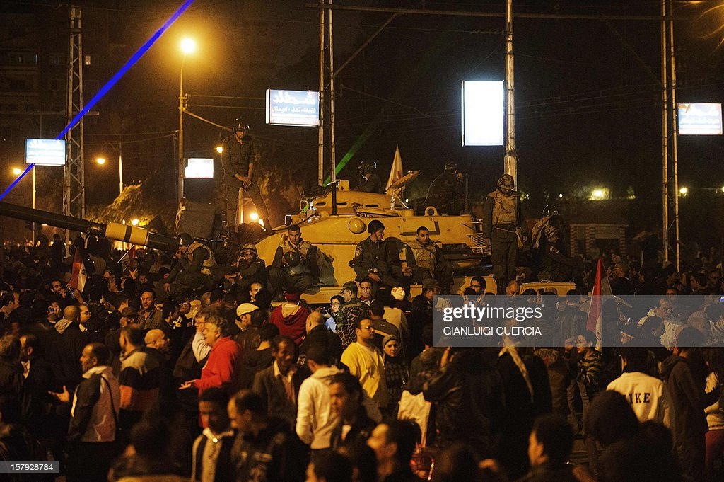 Egyptian army soldiers stand on the top of an army tank as thousands of protesters walk in the streets in front of the presidential palace on December 7, 2012 in Cairo. Thousands of protesters broke through a barbed-wire perimeter protecting Morsi's palace, as his vice-president hinted at a possible compromise aimed at calming the seething crisis dividing Egypt.