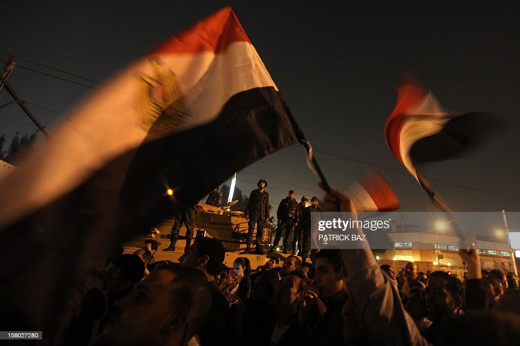 Egyptian army soldiers stand on top of a tank as opposition supporters and protesters wave national flags outside the presidential palace on December 9, 2012 in Cairo. Egypt's main opposition parties were to meet to decide whether to keep up street protests against President Mohamed Morsi after the Islamist leader made a key concession in the crisis dividing the nation. AFP PHOTO/PATRICK BAZ