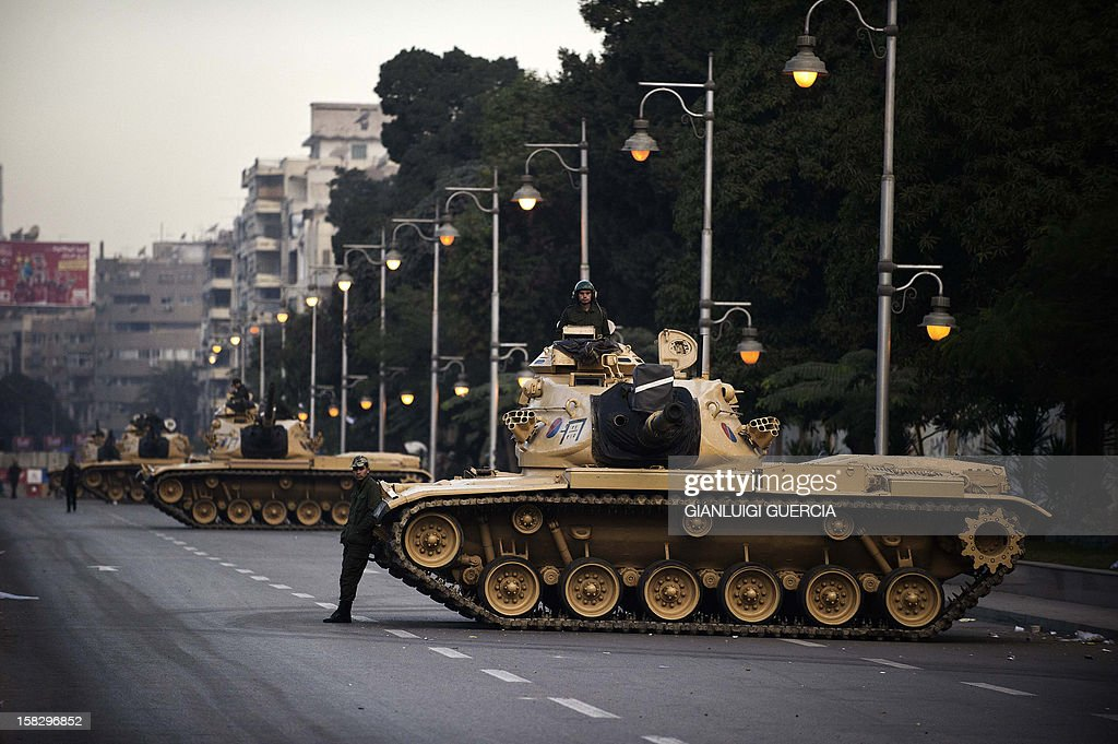 Egyptian army tanks are deployed outside the presidential palace in Cairo on December 13, 2012. Egypt's crisis showed no sign of easing as the army delayed unity talks meant to ease political divisions and the opposition set near-impossible demands for taking part in a looming constitutional referendum. AFP PHOTO/GIANLUIGI GUERCIA