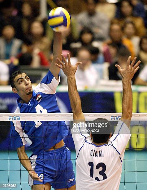 Egyptian attacker Abdelnaeim Salah spikes the ball over Italian Andrea Giani during the World Cup men's volleyball tournament at the Okayama General...