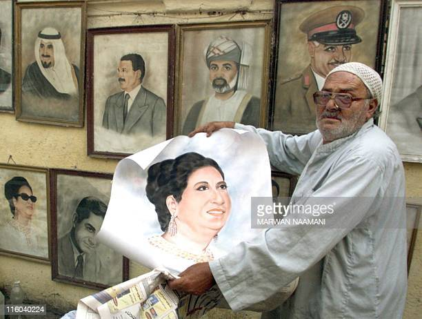 Egyptian Bader Othman proudly shows a watercolour of the late Egyptian Diva Umm Kulthum which he painted at his openair gallery on a pavement in...