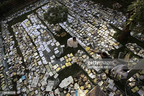 Egyptian book restorers layout burnt and damaged books to dry them in the garden of the Institute of Egypt in central Cairo on December 19 2011 after...
