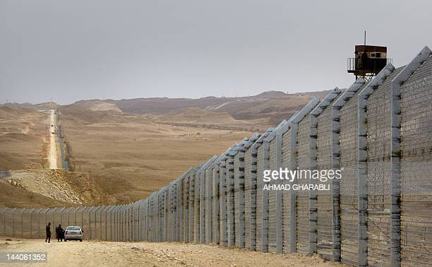 Egyptian border guards observe from a watch tower as their Israeli counterparts supervise the construction of a border fence along Israel's border...