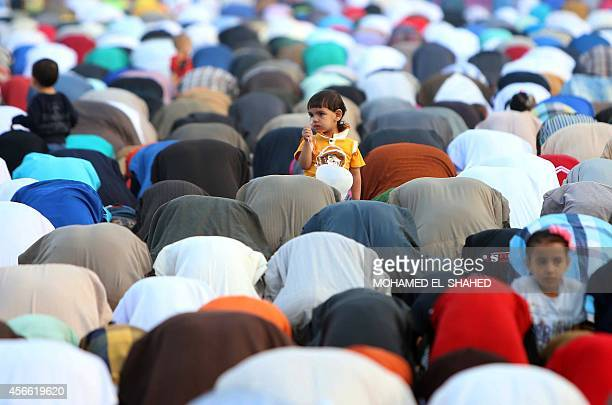 Egyptian children stand among Muslims praying on the first day of Eid alAdha or the Festival of Sacrifice which marks the end of the Hajj pilgrimage...