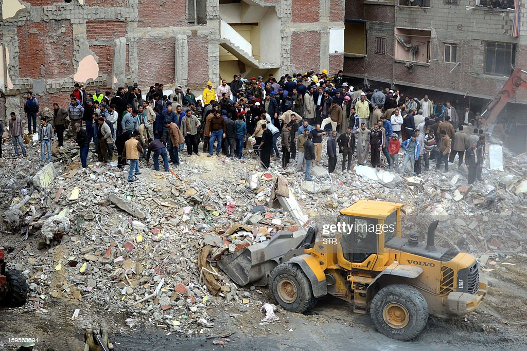Egyptian civilians and emergency services sift through the rubble of a building housing 24 families in the Maamura district of Alexandria which collapsed in the early hours on January 16, 2013. At least five people were killed when the 12-storey building collapsed in the Egyptian coastal city of Alexandria with dozens believed trapped under the rubble, a security official told AFP.