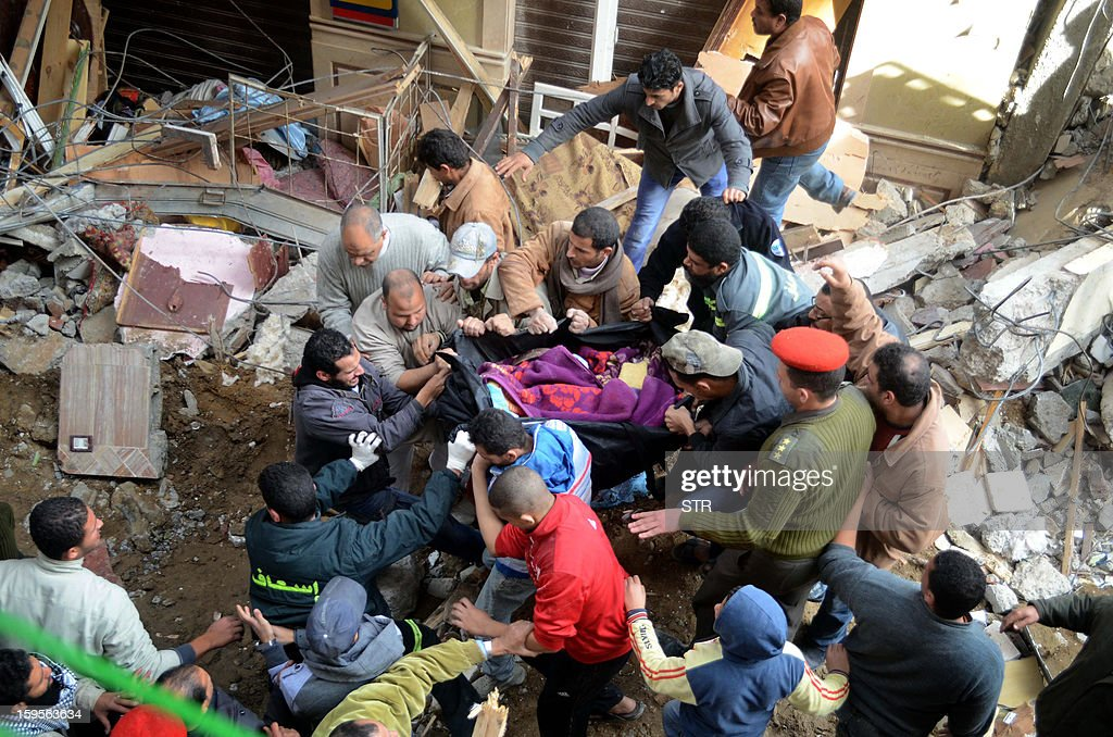 Egyptian civilians and emergency services try to rescue survivors after a building housing 24 families in the Maamura district of Alexandria collapsed in the early hours on January 16, 2013. At least five people were killed when the 12-storey building collapsed in the Egyptian coastal city of Alexandria with dozens believed trapped under the rubble, a security official told AFP.