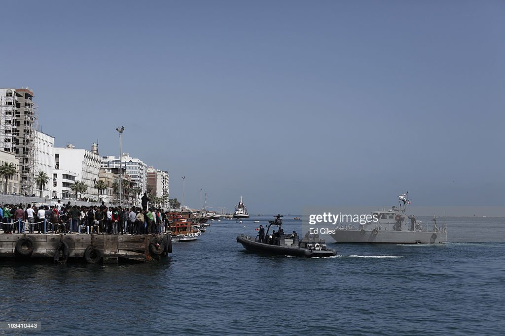 Egyptian coast guard vessels patrol the Suez Canal as residents of Port Said gather at a dock to demonstrate after the announcement of the final verdict in the case of the Port Said football massacre, on March 9, 2013, in Port Said, Egypt. Over seventy football fans of the Al Masry team were killed during a stadium brawl that took place after a match between the Al Masry and Al Ahly teams in the northern Egyptian city in February 2012. Two senior police officers, the Port Said Security Director Essam Samak and head of the Port Said Water Bodies Security Department, Mohammed Saad, received 15 year sentences, while seven other police officers were acquitted. Five Port Said citizens received life sentences on Saturday, and twenty one civilian death sentences handed down in a January ruling on the same case were confirmed. (Photo by Ed Giles/Getty Images).