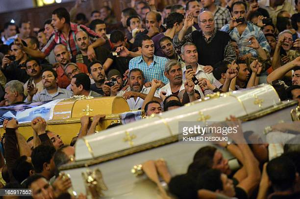 Egyptian Coptic Christians carry the coffins of two of the four Christians killed in sectarian clashes in AlKhusus earlier this week during the...