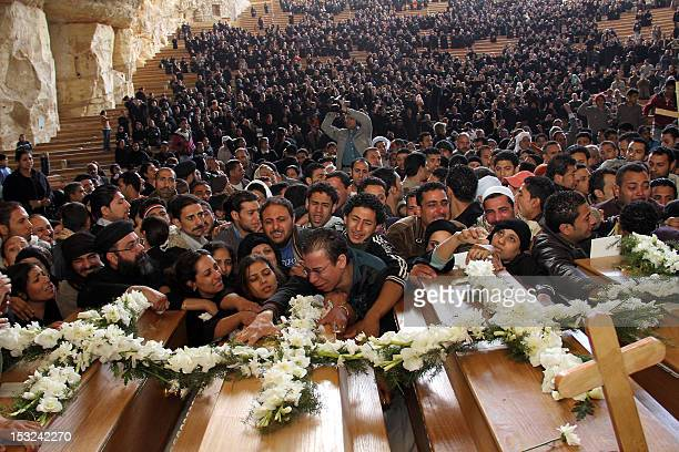 Egyptian Coptic Christians grieve over the coffins of relatives during a mass funeral for victims killed during sectarian clashes at the Samaan...