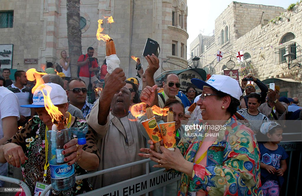 Egyptian Coptic Christians watch a live broadcast of the 'Holy Fire' ceremony in the Church of the Holy Sepulchre in Jerusalem as they stand outside the Church of the Nativity in the biblical West Bank town of Bethlehem on April 30, 2016, during the Orthodox Easter. The ceremony is marked by the appearance of 'sacred fire' in the two cavities on either side of the Holy Sepulchre, in the Church of the Sepulchre in Jerusalem, and Christians all over the world light candles representing this 'Holy Fire'. The Holy Sepulchre in Jerusalem is the site of the tomb of Jesus Christ according to Christian tradition. / AFP / MUSA
