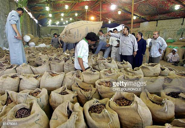 Egyptian dates wholesales men buy different varieties of this dry fruit at a makeshift warehouse to be sold later in the streets in Cairo during a...