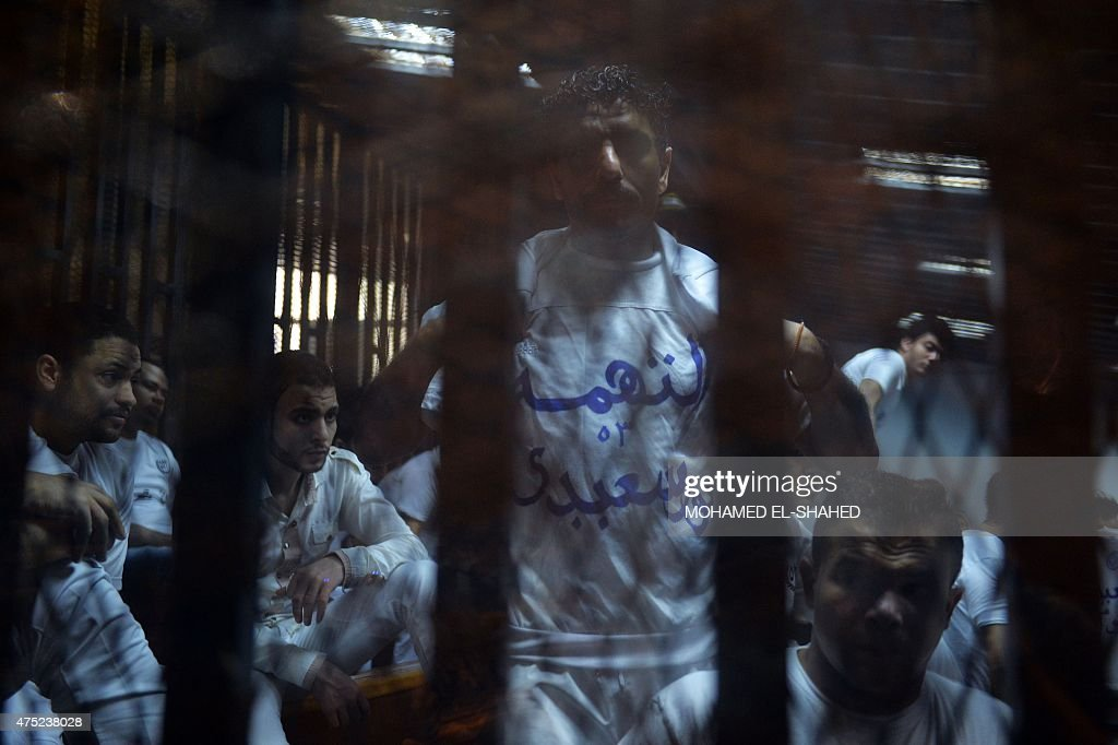Egyptian defendants one showing his Tshirt reading 'my charge is being from Port Said' wait behind bars during their retrial over a 2012 stadium riot...