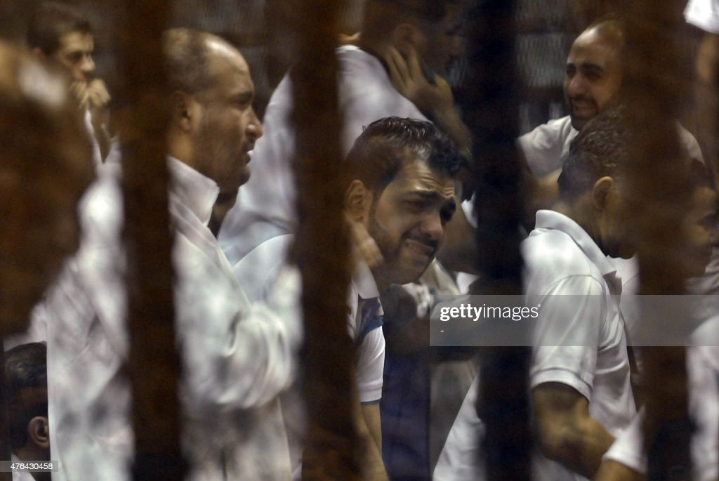 Egyptian defendants react behind bars after the verdict in their retrial over a 2012 stadium riot in the canal city of Port Said that left 74 people...