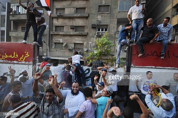 Egyptian demonstrators climb on on September 9 2011 on a wall recently built outside the Israeli embassy in Cairo to protect the building Around 1000...