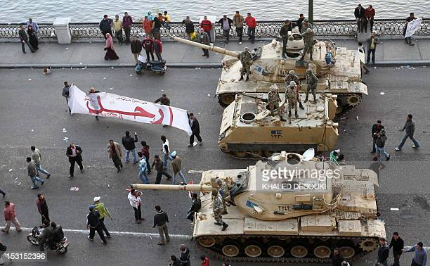 Egyptian demonstrators demanding the ouster of President Hosni Mubarak wave a banner reading 'LEAVE' next to Egyptian army tanks in Cairo on January...