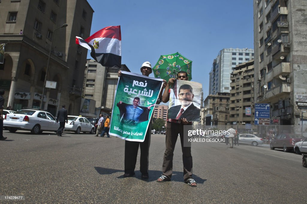Egyptian demonstrators hold portraits of ousted president Mohamed Morsi as they stand in the middle of the street in Cairo on July 22, 2013, following a press conference by the family of Morsi is to take legal action against Egypt's army chief, General Abdel Fattah al-Sisi, for 'kidnapping' the Islamist president. AFP PHOTO / KHALED DESOUKI