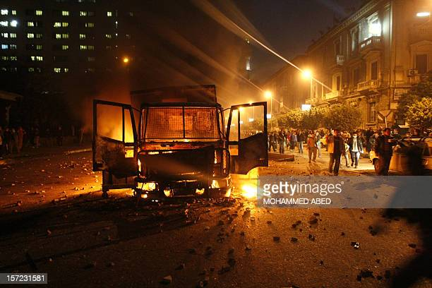 Egyptian demonstrators shout slogans next to a burning riot police vehicle in Cairo on January 28 2011 ABED