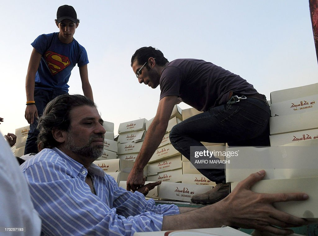 Egyptian director and film writer, Khaled Youssef (L) helps to distribute Ramadan meal boxes to the protesters who gather in Tahrir square on July 10, 2013 in the Egyptian capital Cairo.