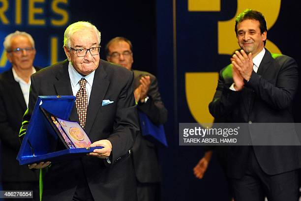 Egyptian director Mohamed Abdul Aziz receives an award as his son Egyptian actor Karim Abdul Aziz claps during the opening ceremony of the Alexandria...