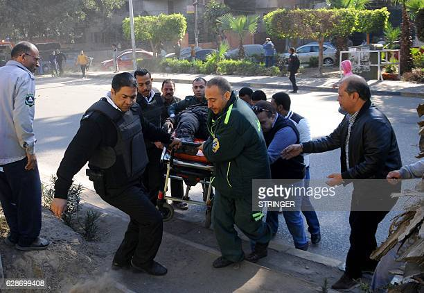 Egyptian emergency services carry a wounded victim at the site of a bomb attack next to a police checkpoint in the western Talibiya district of the...