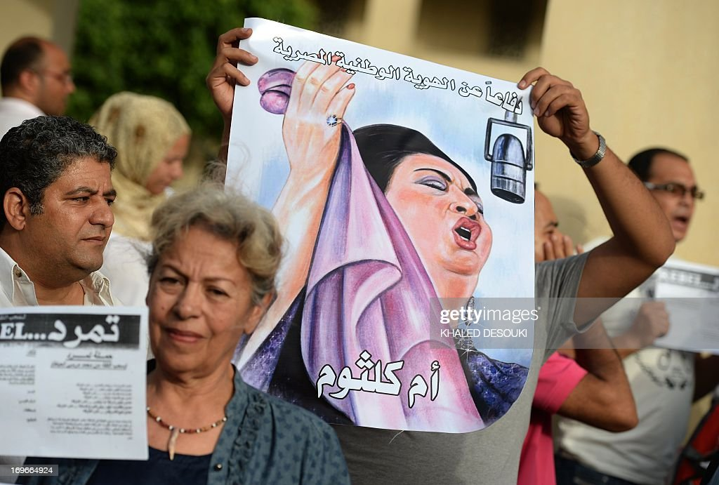 Egyptian employees of the Cairo Opera House and opponents Islamist President Mohamed Morsi hold a portrait of late Egyptian singer Umm Kulthum, known in Arabic as Kawkab al-Sharq 'Star of the East', during a demonstration inside the Opera's compound in Cairo on May 30, 2013 following the dismissal by Egyptian Culture Minister Alaa Abdelfattah of the head of the opera house Ines Abdel-Dayem. The employees are against her dismissal and dont want someone else to replace Abdel-Dayem. AFP PHOTO / KHALED DESOUKI
