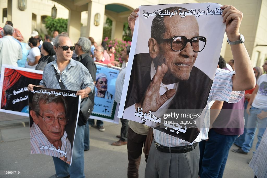 Egyptian employees of the Cairo Opera House and opponents of Egypt's Islamist president Mohamed Morsi hold a portrait of the late Nobel Prize for Literature, Egyptian writer Naguib Mahfouz (R) and late Egyptian film director Youssef Chahine (L) during a demonstration inside the Opera's compound in Cairo on May 30, 2013 following the dismissal by Egyptian Culture Minister Alaa Abdelfattah of the head of the opera house Ines Abdel-Dayem. The employees are against her dismissal and don't want someone else to replace Abdel-Dayem. AFP PHOTO / KHALED DESOUKI