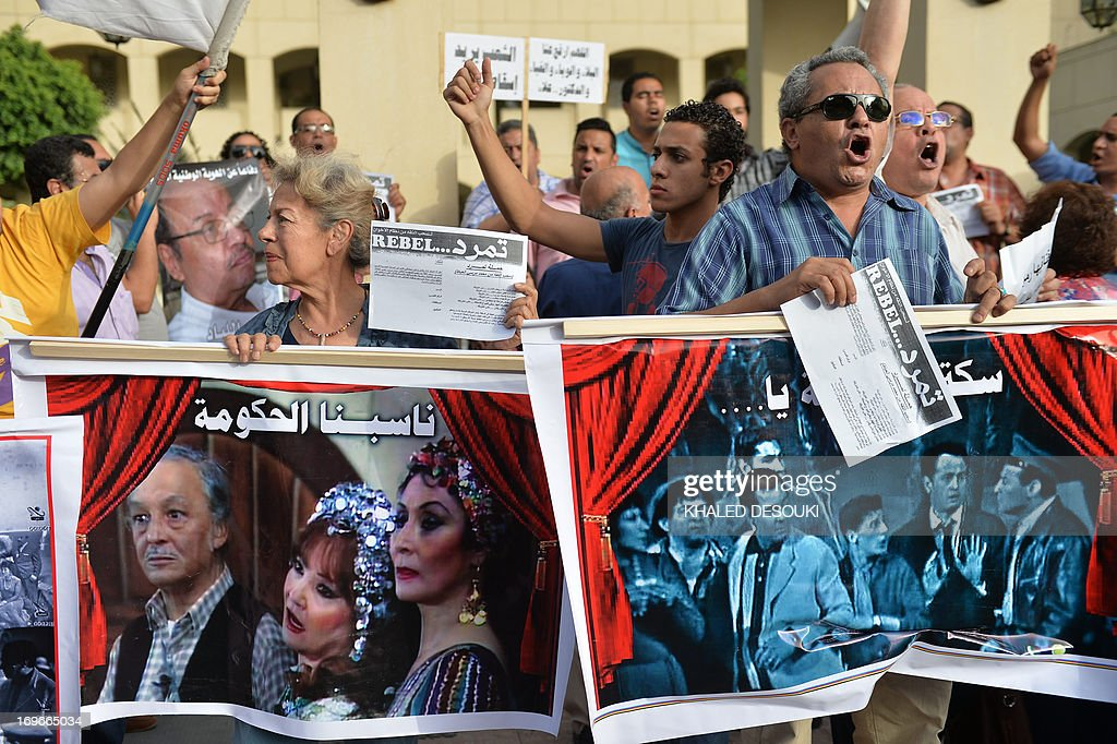 Egyptian employees of the Cairo Opera House and opponents of their Islamist President Mohamed Morsi hold placards during a demonstration inside the Opera's compound in Cairo on May 30, 2013 following the dismissal by Egyptian Culture Minister Alaa Abdelfattah of the head of the opera house Ines Abdel-Dayem. The employees are against her dismissal and don't want someone else to replace Abdel-Dayem.