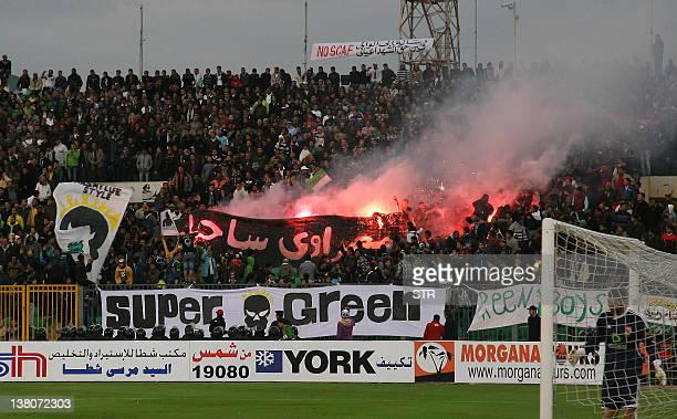 Egyptian fans of AlMasry light flares during a football match against AlAhly in Port Said on February 1 2012 At least 74 people were killed and...
