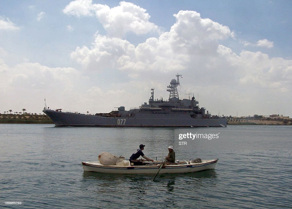 Egyptian fishermen row their boat near the Russian amphibious warfare ship Admiral Nevelsky as it crosses the Suez canal on its way to the Mediterranean sea on May 15, 2013 at Egypt's port town of Ismailia.