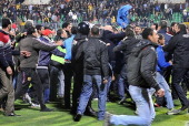 Egyptian football fans rush to the pit during riots that erupted after a football match between AlMasry and AlAhly teams in Port Said 220 kms...