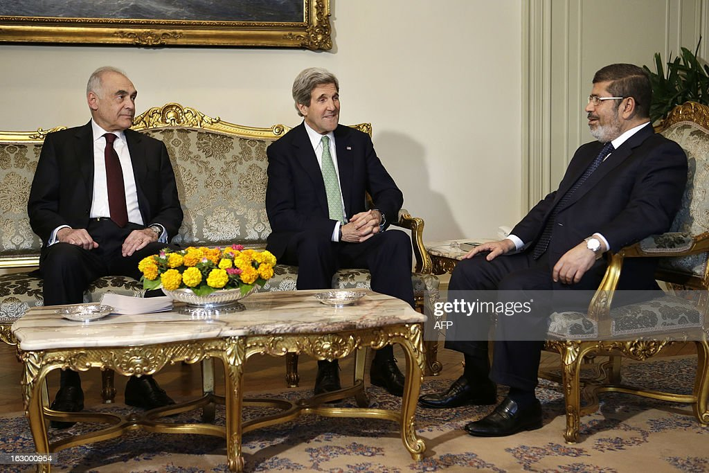 Egyptian Foreign Minister Mohammed Kamel Amr and US Secretary of State John Kerry (C) meets with Egyptian President Mohamed Morsi at the presidential palace in Cairo on March 3, 2013. Kerry met the Egyptian president as he wrapped up a trip to Cairo, where he urged divided factions to reach a consensus that would pave the way for economic recovery.