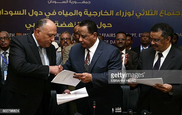 Egyptian Foreign Minister Sameh Shoukri shakes the hand of Sudanese Foreign Minister Ibrahim Ghandour in the presence of Ethiopian Foreign Minister...