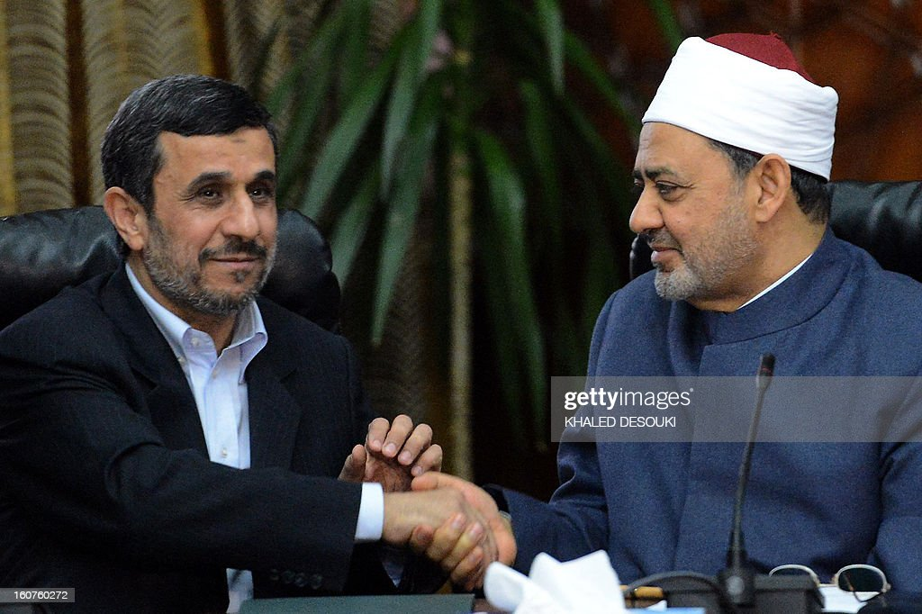 Egyptian Grand Imam of Al-Azhar Sheikh Ahmed al-Tayeb (R) shakes hands with Iranian President Mahmoud Ahmadinejad during a meeting at Al-Azhar headquarters in Cairo on February 5, 2013. Ahmadinejad held talks in Cairo on the divisive issue of Syria's war, as he kicked off the first visit to Egypt by an Iranian president since 1979. AFP PHOTO / KHALED DESOUKI