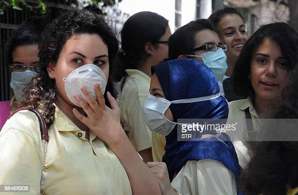Egyptian high school students girls wear protective masks as they leave school at the end of the first day of exams in Cairo's Zamalek district on...