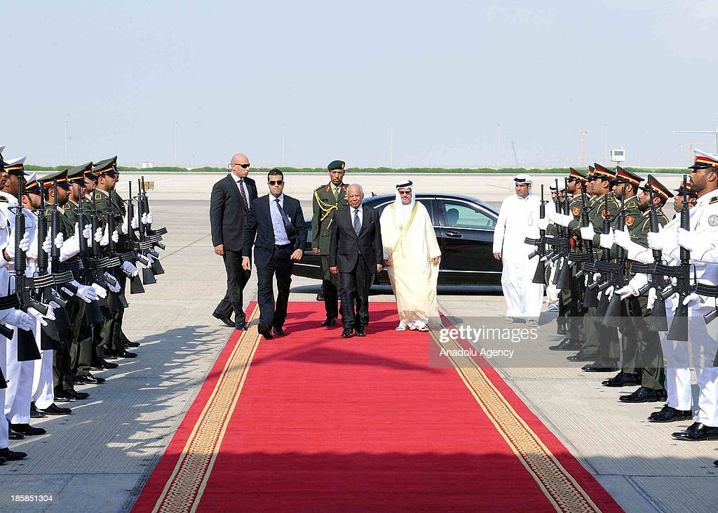 Egyptian Interim Prime Minister Hazem Al Beblawi (C) is welcomed by UAE Minister of State for Foreign Affairs Anwar Mohammed Qarqash (2nd R) upon his arrival on October 25, 2013 in Abu Dhabi, United Arab Emirates. Hazem Al Beblawi arrived in Abu Dhabi on Friday for a three-day visit to hold talks on bilateral cooperation with UAE President Sheikh Khalifa bin Zayed al-Nahyan, Vice-President and Prime Minister Sheikh Mohamed bin Rashid al-Maktoum and Abu Dhabi Crown Prince Mohamed bin Zayed al-Nahyan.