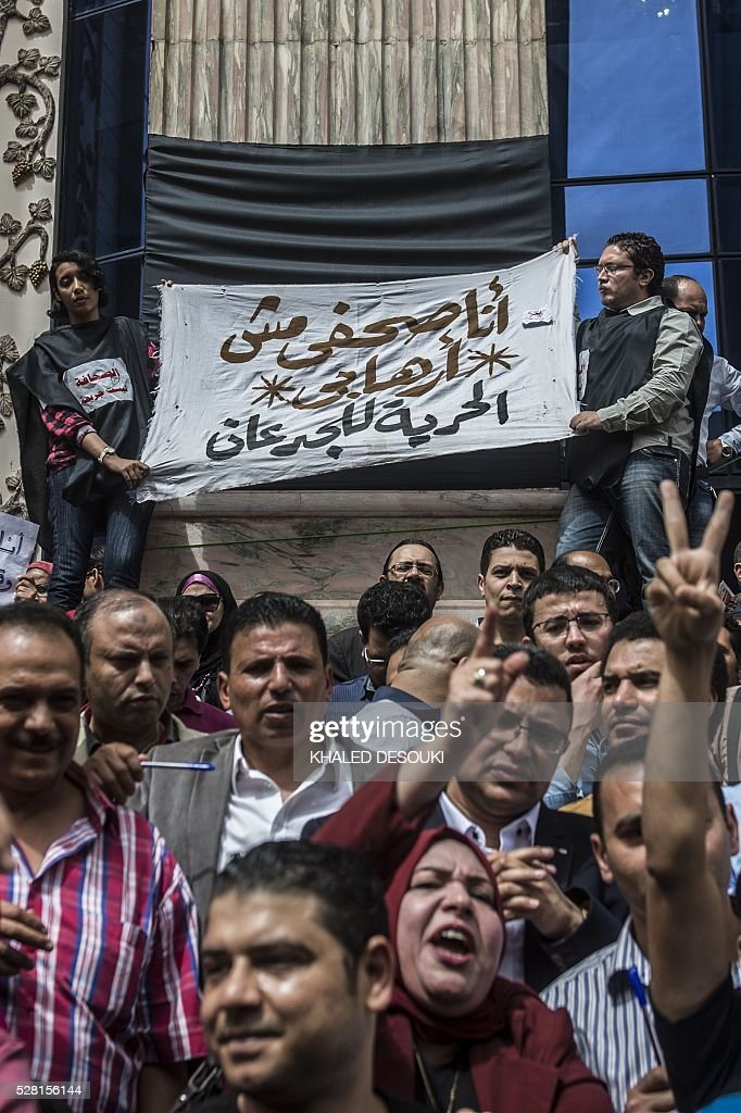 Egyptian journalists hold a banner reading in Arabic: 'I am a journalist not a terrorist' as they demonstrate outside the union headquarters in Cairo on May 4, 2016, demanding the sacking of the interior minister two days after the police stormed the syndicate and arrested two journalists. / AFP / KHALED