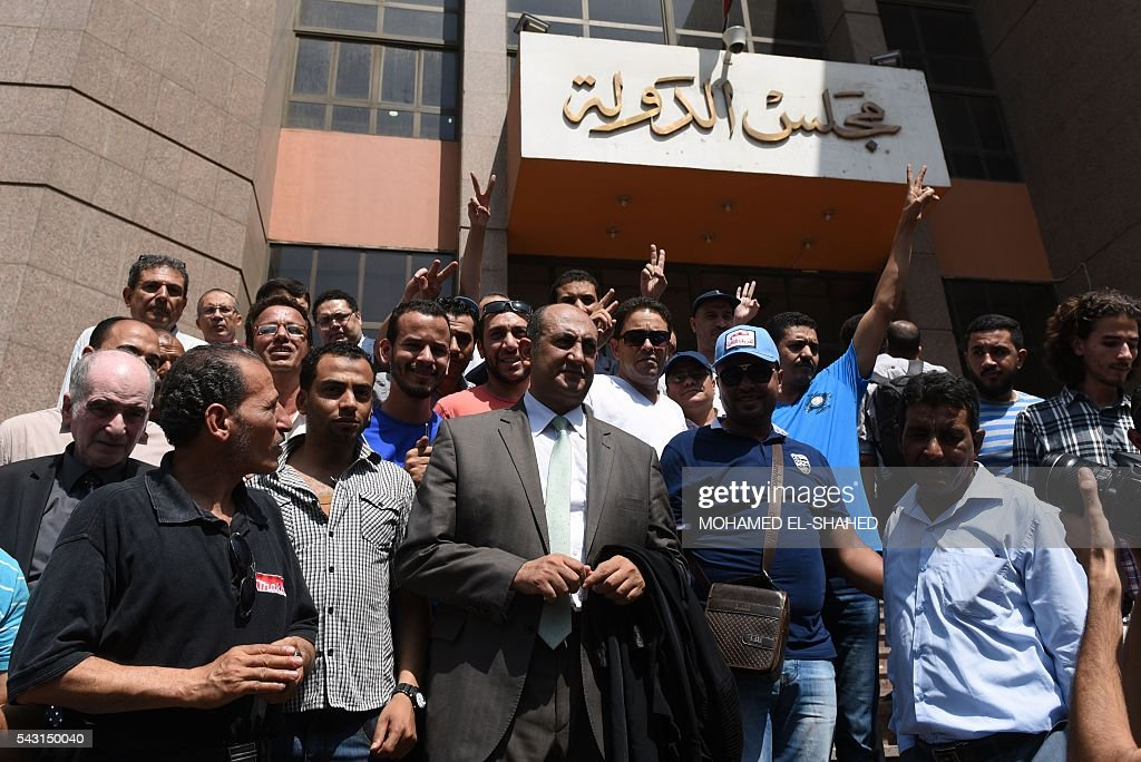 Egyptian lawyer and leftist opposition figure Khaled Ali (C) stands among people outside the State Council's building, Egypt's highest administrative court, in Cairo on June 26, 2016, after the court postponed to July 3 the hearing of the government's appeal against the decision to block the controversial handover of two uninhabited Red Sea islands to Saudi Arabia. The deal over the islands of Tiran and Sanafir prompted some of the largest public protests in two years when it was signed in April. The country's State Council ruled on June 21 that the islands, strategically situated at the mouth of the Gulf of Aqaba, must remain under Egyptian sovereignty. / AFP / MOHAMED