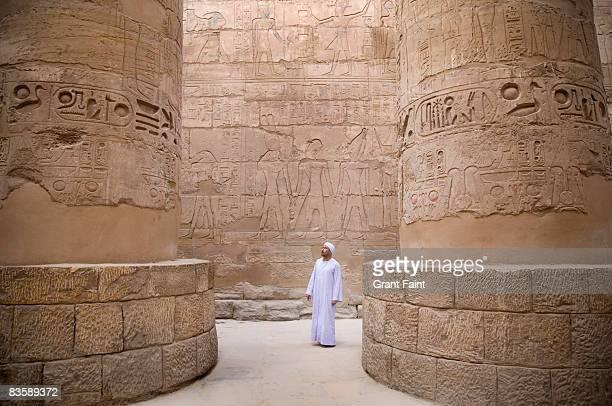 egyptian man standing in Karnak temple columns