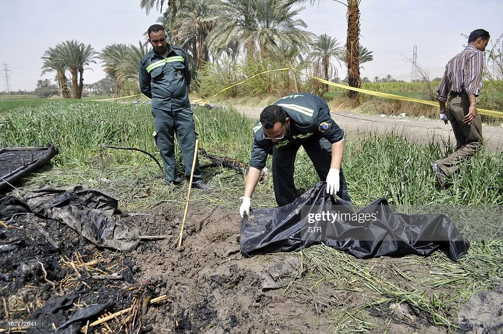 Egyptian medics collect remains from the site of a hot air balloon accident in Luxor on February 26, 2013. A hot air balloon exploded and plunged to earth at Egypt's ancient temple city of Luxor during a sunrise flight, killing up to 19 tourists, including Asians and Europeans, sources said.