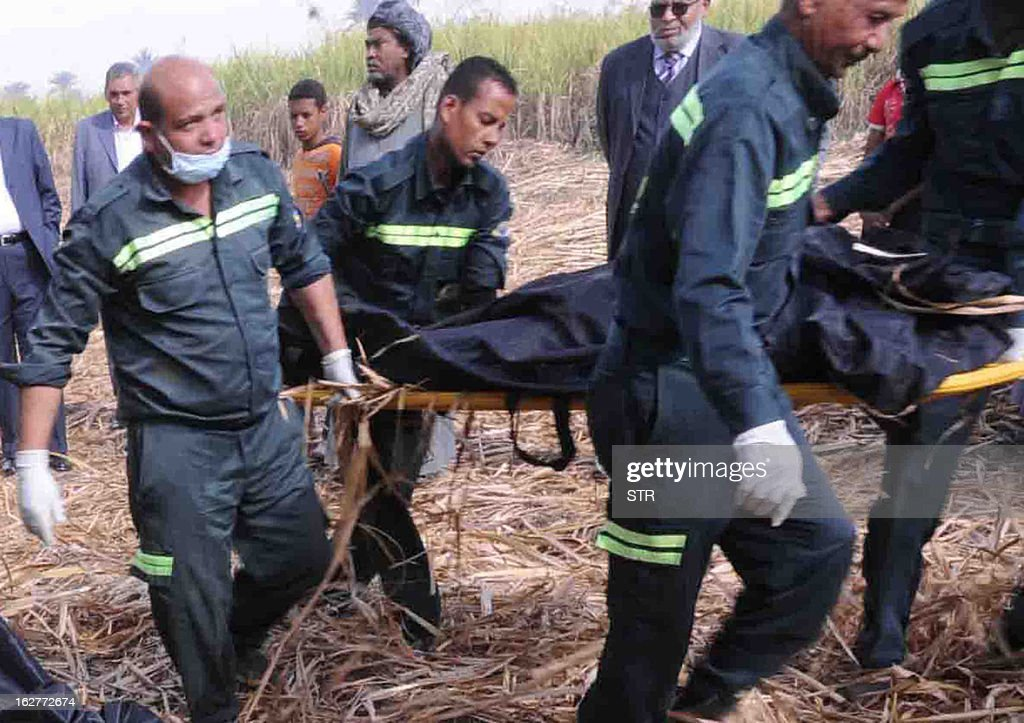 Egyptian medics remove the body from a victim from the site of a hot air balloon accident in Luxor on February 26, 2013. A hot air balloon exploded and plunged to earth at Egypt's ancient temple city of Luxor during a sunrise flight, killing up to 19 tourists, including Asians and Europeans, sources said. AFP PHOTO /STR