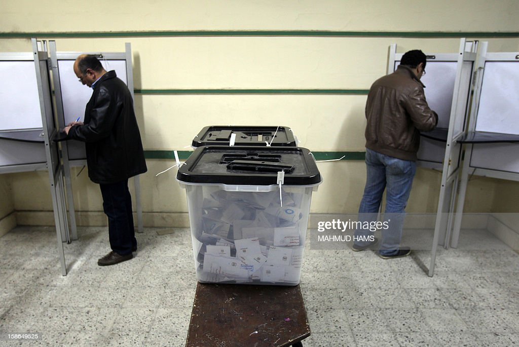 Egyptian men cast their ballots during the second round of a referendum on a new draft constitution in Giza, south of Cairo, on December 22, 2012. Egyptians are voting in the final round of a referendum on a new constitution championed by President Mohamed Morsi and his Islamist allies against fierce protests from the secular-leaning opposition.