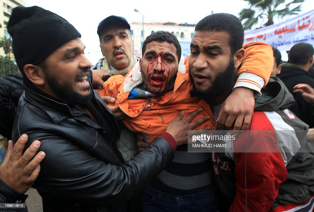 Egyptian men help a wounded comrade during clashes between opponents and supporters of President Mohamed Morsi in the Mediterranean coastal city of Alexandria on December 21, 2012. Running clashes between rival protesters erupted in Egypt's second city Alexandria, on the eve of the final round of a referendum on a new constitution backed by the ruling Islamists.