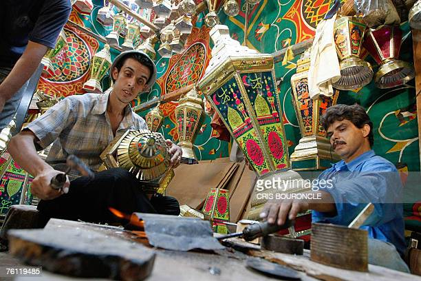 Egyptian men make traditional tin lanterns known as Fawanis Ramadan in the back of a shop in old Cairo 16 August 2007 as preparations begin for the...