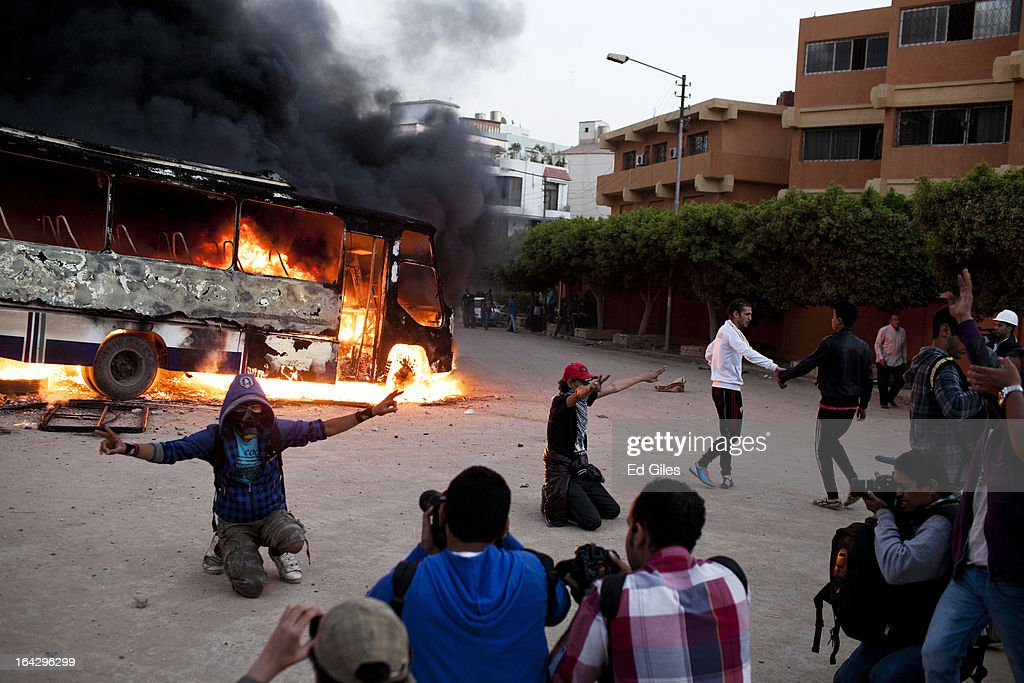 Egyptian men pose for photographers before a burning bus reportedly belonging to the Muslim Brotherhood during clashes between opposition demonstrators and supporters of the Muslim Brotherhood on March 22, 2013 in Cairo, Egypt. Opposition demonstrators converged on the headquarters of the Muslim Brotherhood in the Cairo suburb of Muqattam to protest against the government of President Mohammed Morsi, who is closely connected to the Muslim Brotherhood movement.