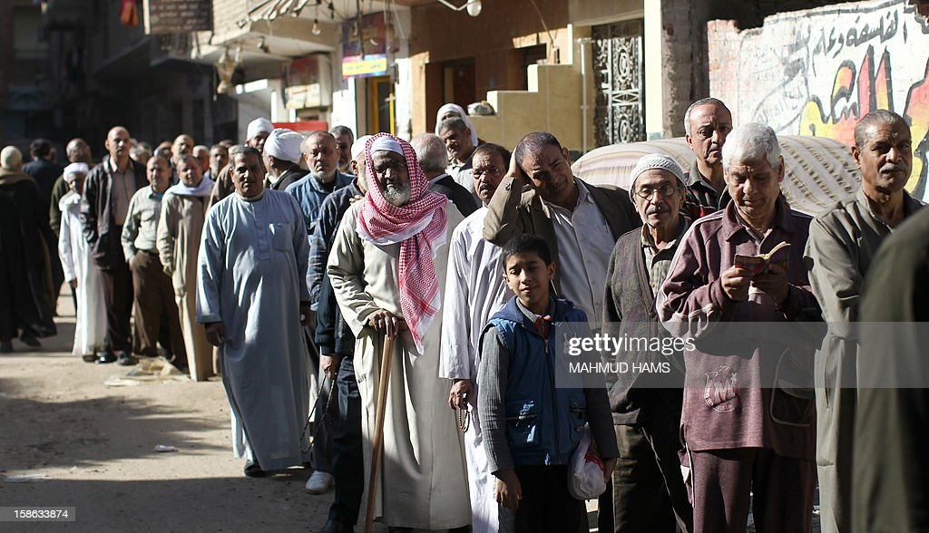 Egyptian men queue outside a polling station during the second round of a referendum on a new draft constitution in Giza, south of Cairo, on December 22, 2012. Egyptians are voting in the final round of a referendum on a new constitution championed by President Mohamed Morsi and his Islamist allies against fierce protests from the secular-leaning opposition.